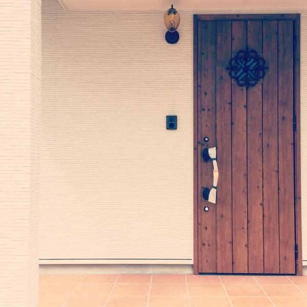 白い外壁に映える木目調の玄関ドア